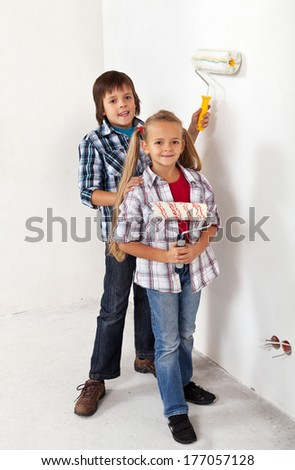 Kids painting their room with paint rollers - standing together in a new house - stock photo