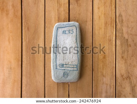 kids phone toy. stone phone on the wooden teak table. drawing on stone. primitive phone. communication, imagination, - stock photo