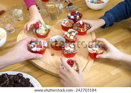 Kids picking their favourite decorated cupcake from a heart shaped cutting board at a birthday party - stock photo