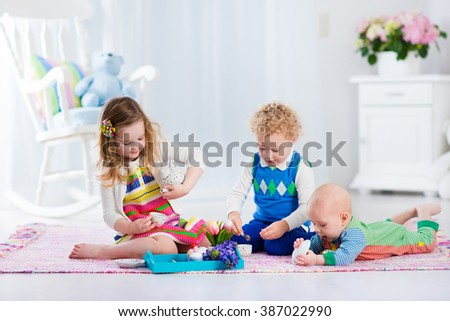 Kids play at home. Children playing in white sunny nursery. Little girl having fun at doll tea party with her brothers. Siblings making lunch for toy bear. Toddler, preschooler and baby at day care. - stock photo
