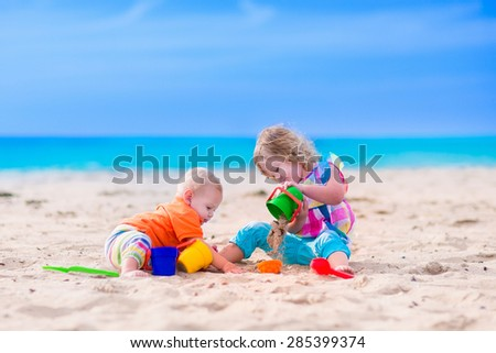 Kids play on a beach. Children building sand castle on tropical island. Summer water fun for family. Boy and girl with toy buckets and spade at the sea shore. Ocean vacation with baby and toddler kid. - stock photo