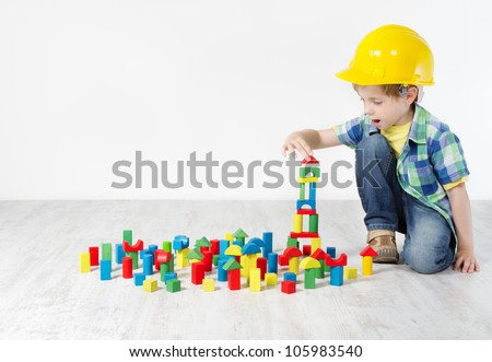 Kids Play Room, Child in Hard Hat Playing Building Blocks Toys. Development and Construction Concept - stock photo