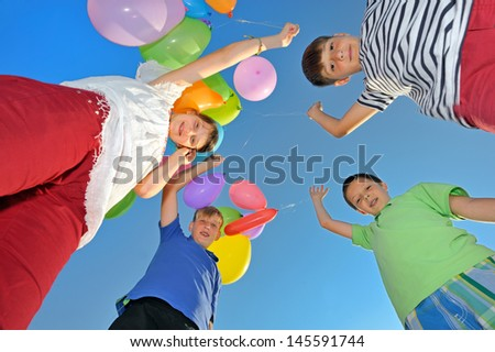 kids play with balloons on field - stock photo