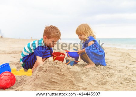 kids play with sand on summer beach