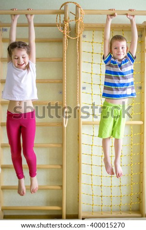 Kids playing and hanging on horizontal bar by gymnastic equipment