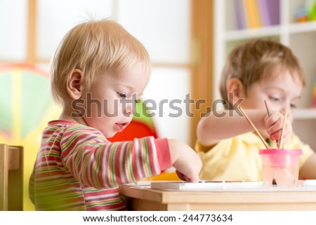 kids playing and painting at home or kindergarten or playschool - stock photo