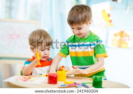 kids playing and painting at homeor kindergarten or playschool or daycare - stock photo