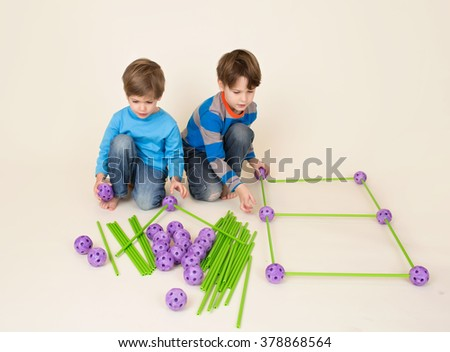 Kids playing and sharing construction or engineering set pieces  - stock photo