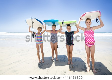 Kids playing at the beach together while on vacation holding their boogie boards - stock photo