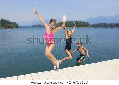 Kids playing at the lake on their summer vacation  - stock photo