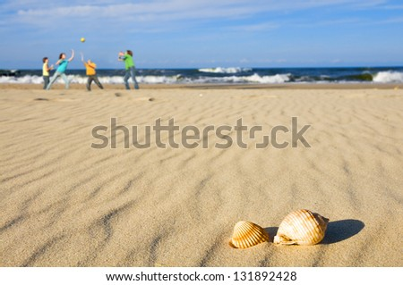 Kids playing ball on the beach with shells - stock photo