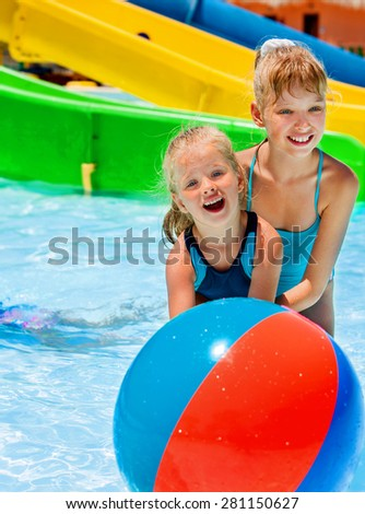 Kids playing beach ball in water slide at aquapark. Summer holiday.