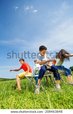 Kids playing game and sit fast on chairs outside - stock photo