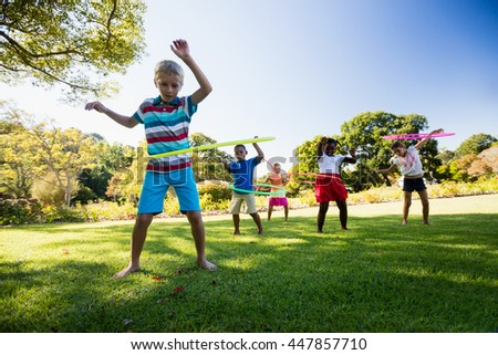 Kids playing hoop together during a sunny day at park - stock photo