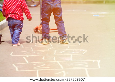 kids playing hopscotch on playground outdoors, children outdoor activities