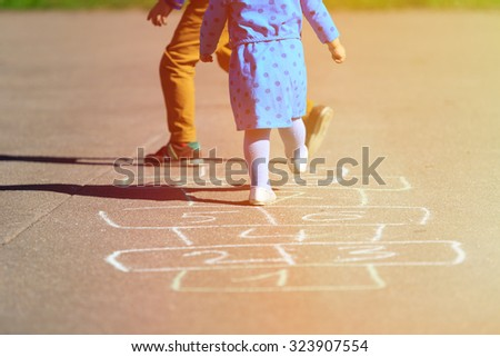 kids playing hopscotch on playground outdoors, children outdoor activities - stock photo
