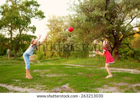 Kids playing in a suburban neighborhood. Two sisters or girlfriends throwing the ball to each other. - stock photo