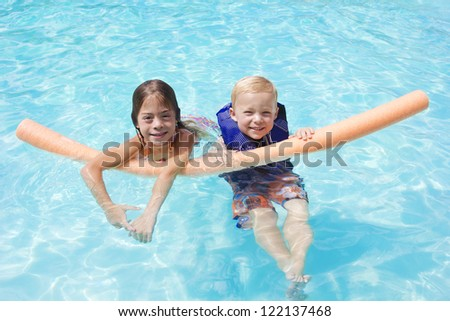 Kids Playing in the swimming pool together - stock photo