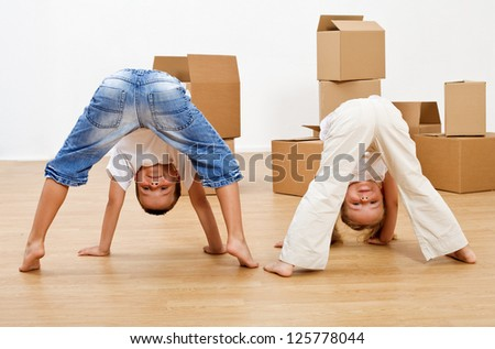 Kids playing in their new home having fun in front of cardboard boxes - stock photo