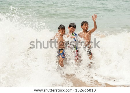 kids playing in water against the waves