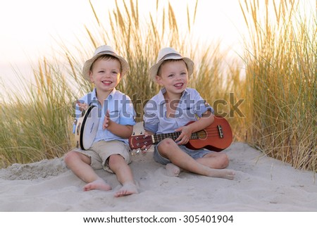 kids playing music in the dunes - stock photo