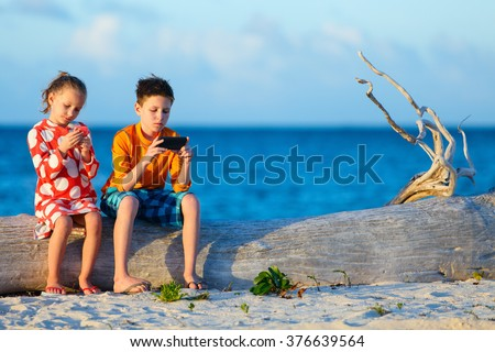 Kids playing on a portable game device or smartphone at beach - stock photo