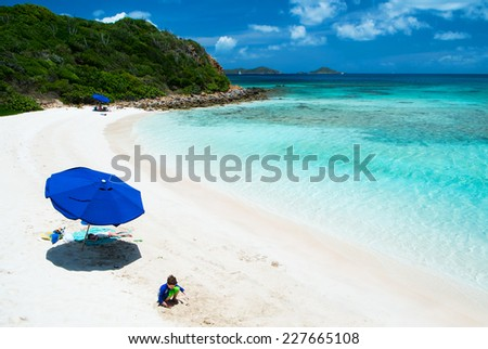 Kids playing on picture perfect beach with blue umbrella, white sand, turquoise ocean water and blue sky at tropical island in Caribbean - stock photo