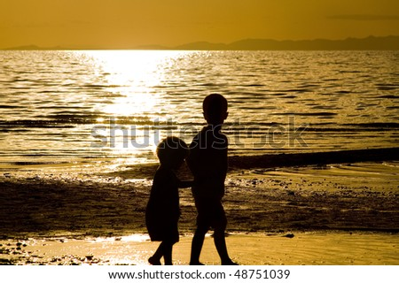 Kids playing on the beach - silhouette shot - stock photo