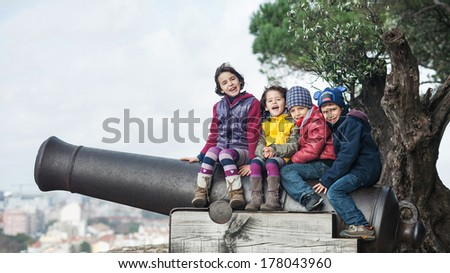 "Kids playing outdoors sit on gun in the park of ""Castle Sao Jorge"". Lisbon, Portugal. - stock photo"