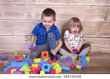 Kids playing toy blocks - stock photo