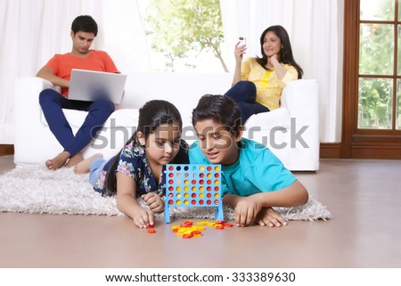 Kids playing while parents sit on sofa - stock photo