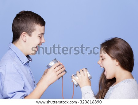 Kids playing with a can as a telephone on blue background
