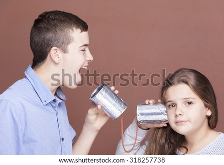 Kids playing with a can as a telephone on brown background - stock photo