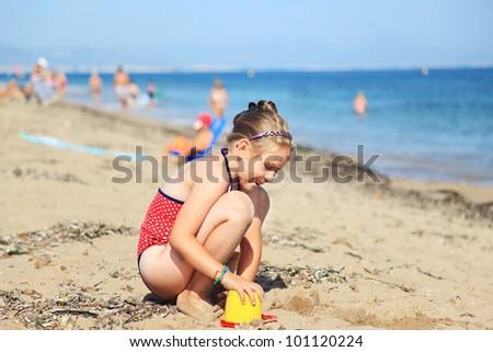 Kids playing with plastic toys on the beach - stock photo
