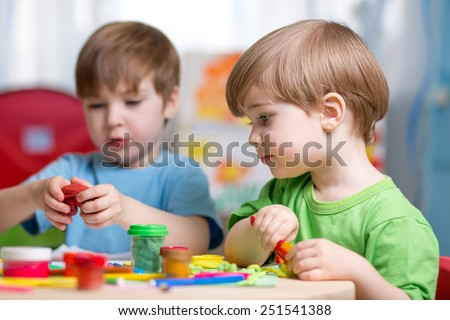 kids playing with play clay at home or kindergarten or playschool - stock photo