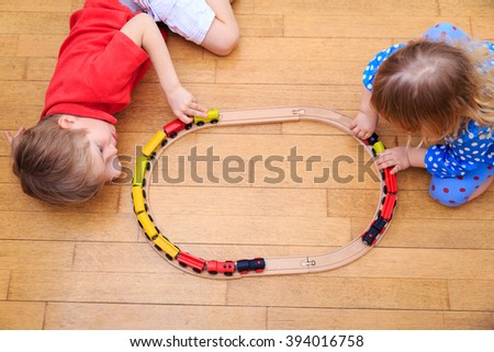 kids playing with railroad and trains indoor - stock photo