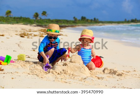 kids playing with sand on summer beach - stock photo