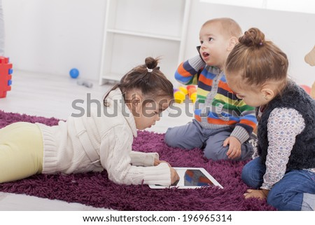 Kids playing with tablet in the room