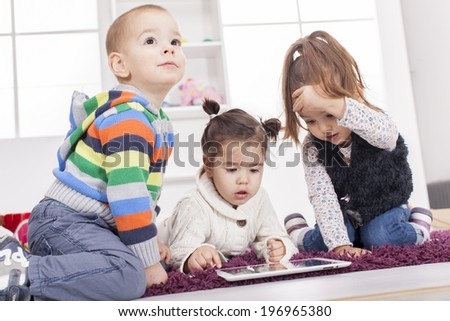 Kids playing with tablet in the room - stock photo