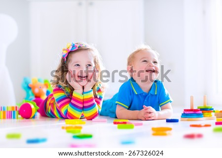 Kids playing with toys. Two children, cute toddler girl and funny baby boy, playing with wooden toy blocks, building towers at home or day care. Educational child toys for preschool and kindergarten. - stock photo