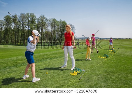 Kids practicing with trainer at golf school at summer day