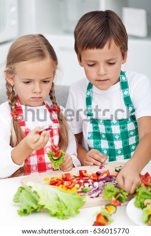 Kids preparing a vegetables snack in the kitchen - roasting veggies on stick, closeup