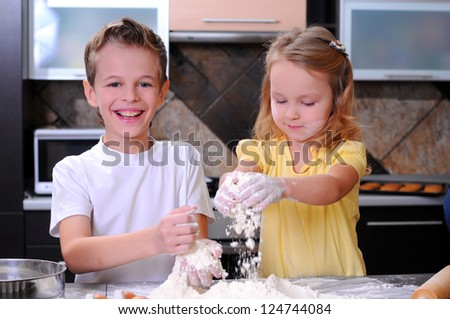 Kids preparing the dough for a cookie, pizza or pasta - having fun breaking the eggs - stock photo
