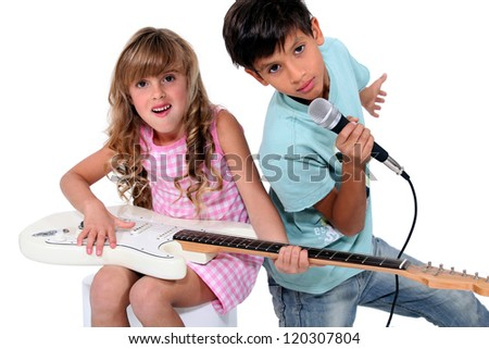 Kids pretending to be in a rock band - stock photo