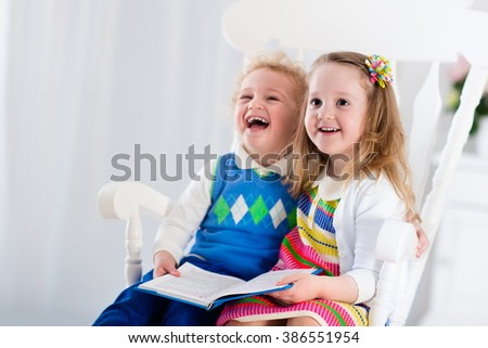 Kids read a book. Children reading books in white chair. Toddler kid and preschooler child doing homework. Little boy and girl study at home after kindergarten. Brother and sister play and laugh. - stock photo