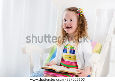 Kids read a book. Children reading books in white chair. Toddler kid playing in white bedroom. Preschooler child doing homework. Smart little girl studying at home after kindergarten or day care.