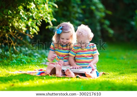 Kids reading a book in summer garden. Children study. Boy and girl play in school yard. Preschool friends playing and learning. Siblings doing homework. Kindergarten kid and toddler read books. - stock photo