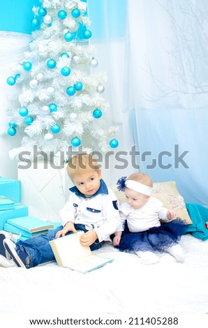 kids reading book in New Year's interior in turquoise and white colors - stock photo