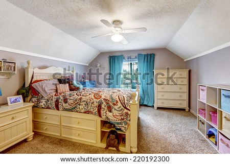 Kids room interior with vaulted ceiling. Wooden bed with drawers. - stock photo