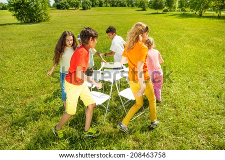 Kids run around playing musical chairs game - stock photo